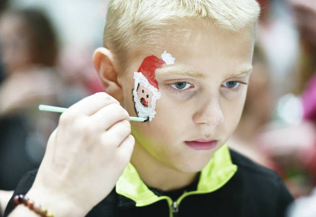 Zacory Wiswell, 10, of Jackson Center, son of Cory and Lori Wiswell, has Santa painted on his face by Madith Barton, of Maplewood, during Christmas In The Village at Jackson Center Local School where Santa visited and there was a tree lighting ceremony held by the Cub Scout Pack 90. The event was held Sunday, Dec. 2.