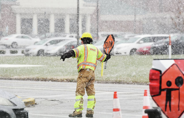 Heavy snow swirls around Roger Cooper, of Centerville, as he directs traffic around roadwork next to Sidney Food Mart Thursday, Dec. 6. Workers were repairing a patch of road dug up by gas crews.