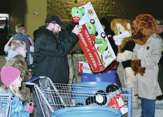 Ross Lewis, of Sidney, puts a toy into a barrel during battle of the mascots held from 6 p.m. to 7 p.m. by Walmart. The mascot to get the most toys won. The mascot battle was part of the Salvation Army's Stuff a Truck campaign to collect toys for kids. The campaign was going on all day Friday, Dec. 7 in front of Walmart. The toys were purchased by Best 1 Tire which is Lewis' employer. Best 1 Tire owner Jeff Pollard has made a tradition of buying several cartloads of toys for the campaign. With Lewis are his children Claire Lewis, left to right, 5, and Corbin Lewis, 9, children of Stephanie Lewis.