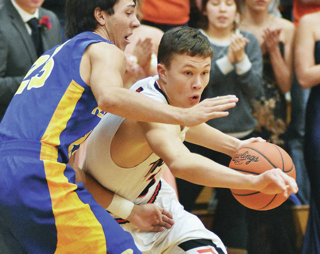 Jackson Center senior guard Trent Platfoot drives with pressure from a Russia defender during a Shelby County Athletic League game on Dec. 8, 2017 in Jackson Center. Platfoot scored 13 points in the Tigers' season-opening win over Russia and 11 points in a loss last Saturday at Columbus Grove.