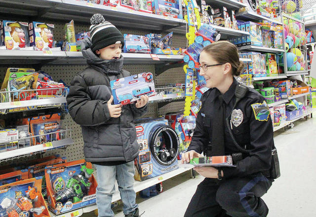 Kevin Kapnick, left, 7, of Sidney, son of Stephanie Kapnick and Jeff Kapnick looks at Thomas the Trains with Sidney Police Officer Rachel Croskrey during Shop With a Cop at Walmart Sunday, Dec. 9. Law enforcement from around the area descended on Walmart to help kids pick out some new clothes and a toy or two during the annual program.
