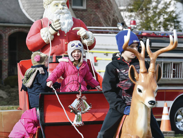 Caleigh Holthaus, third from left, 5, of Minster, takes the reigns of Santa's sleigh in Minster Saturday, Dec. 8. Behind the sleigh is the fire truck that delivered Santa to the Minster gazebo where he listened to gift requests. Riding on one of Santa's reindeer is Mason Berning, far right, 11, of Anna, son of Dennis and Kristi Berning. Climbing into the sleigh are Caleigh's sisters Madison Holthaus, left to right, 1, and Chloe Holthaus, 3, all of Minster, all the children Dan and Jill Holthaus.
