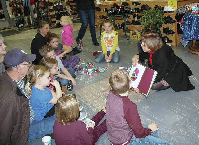 Gateway Arts Council Executive Director Ellen Keyes reads a Christmas story to children at Ron & Nita's recently. Kids also got to meet Santa.