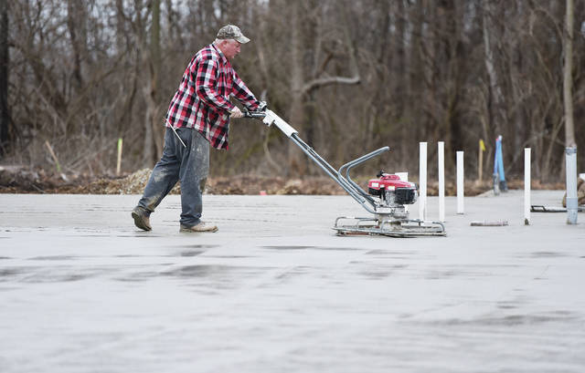 Ron Lange, of St. Henry, power trowels the newly poured concrete floor of the Bob Sargeant and Family Shelby County Animal Shelter and Adoption Center being built along Gearhart Road in Sidney, Friday, Dec. 14. The shimmer of water from morning rain making for wet work.