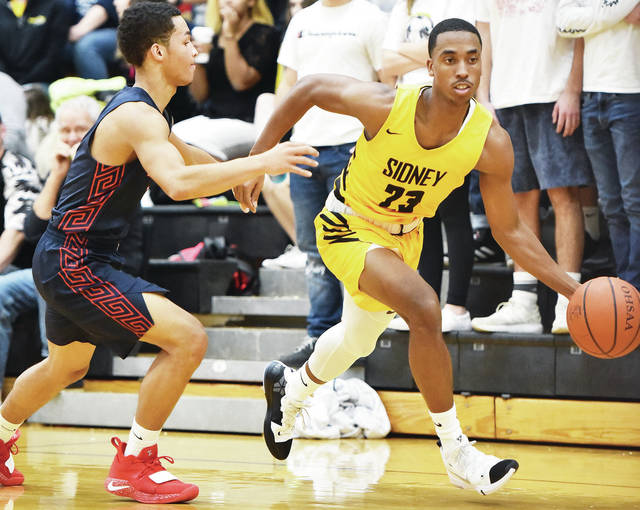 Sidney's Josiah Hudgins heads past Piqua's Qurri Tucker during a Greater Western Ohio Conference American North Division game against on Friday in Sidney.