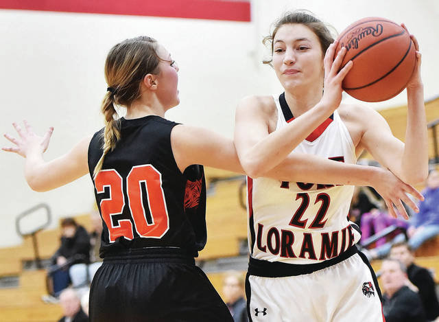 Fort Loramie's Kenzie Hoelscher looks to get around Jackson Center's Kylie Hartle during a Shelby County Athletic League game on Saturday in Fort Loramie.