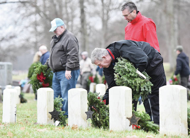 Laying wreaths on veteran's graves during a Wreaths Across America ceremony at Graceland Cemetery Saturday, Dec. 15 are front to back James Myers, of Sidney, Shelby Oaks Club Pro Rob Fridley, and Shelby County Commissioner Bob Guillozet. The day is used to honor veterans accross the U.S..