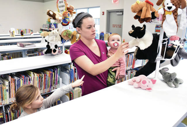 Courtney Burns, center, helps her daughters Ayla Lewis, left, 5, and Gwendolyn Burns, 1, all of Anna, pick out hand puppets to borrow at the Amos Memorial Public Library Wednesday, Dec. 26. The girls received a puppet theatre from Santa so they decided to borrow some puppets to use with it. Ayla is also the daughter of Brandon Lewis. Gwendolyn is also the daughter of Brent Burns.