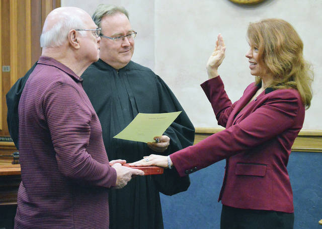 Julie Ehemann, far right, is sworn in to her third term as Shelby County Commissioner by Juvenile Judge Jeff Beigel, center, as her father Robert Rump, of New Bremen, holds a Bible at the Shelby County Courthouse Monday Dec. 24.