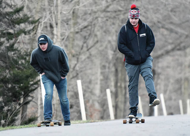 Camam Devandreuil, left, of Piqua, and Ryan Wilder, of Sidney, take advantage of unseasonably warm weather to longboard at Tawawa Park Wednesday, Dec. 26. Longboards are similar to skateboards but are longer and have larger wheels. Temperatures will continue to be relatively high through Monday.