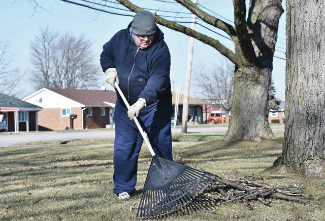Wayne Shoffner, of Sidney, rakes twigs into a pile on his front lawn along South Vandemark Road Sunday, Dec. 30. Shoffner found a lot of twigs and a couple of large branches had been blown down in his yard from the recent wind storm. Shoffner has the view that cleaning up the twigs now will mean less work in the spring.