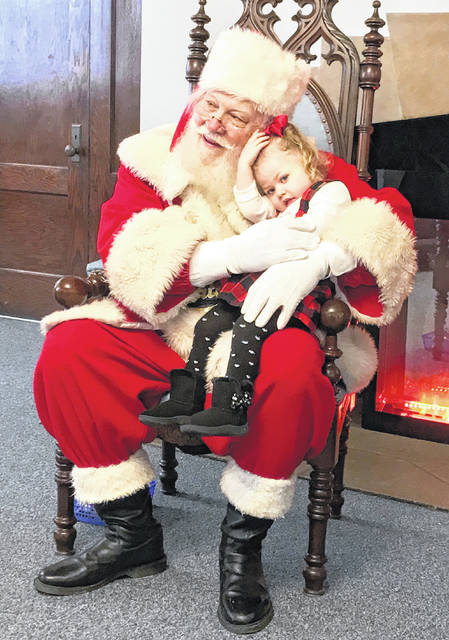 Allison Daniels, 2 ½, daughter of Julia Geuy and Jabar Hudgins, snuggles with Santa at Pleiades 298 OES, Breakfast with Santa, held Dec. 8, 2018, at the Sidney Masonic Temple.