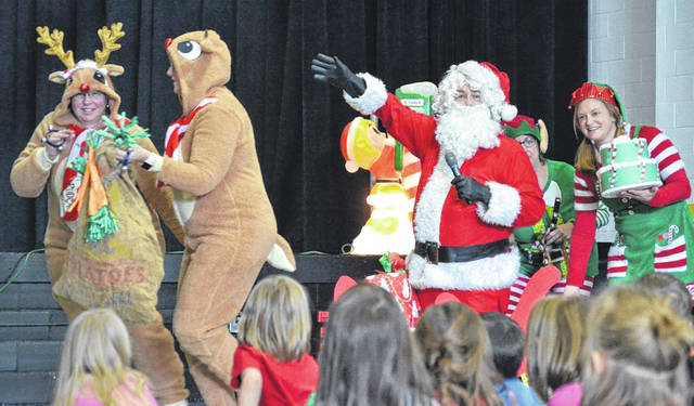 """Northwood Elementary School staff performed """"Christmas with the Footlys"""" for students Tuesday. The skit was written by a staff member Meg Raterman. The Footly family loves Santa so much that they try to capture him so they can throw him a special party. Santa (Superintendent Bob Humble), top photo, watches two of his reindeer portrayed by Cheryl Clark, left, and Kelly Barker. In the photo below, Santa holds a present and a cake as elves (Sarah Steenrod, far left, and Jen Wiford watch in anticipation of the big event."""