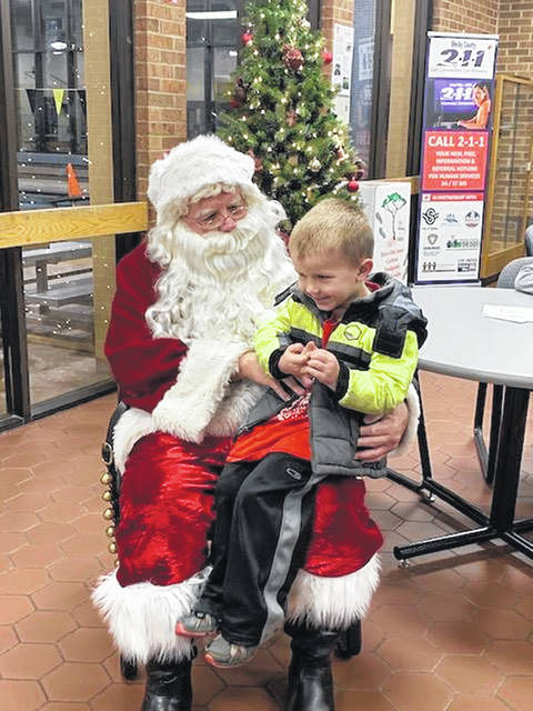 D.J. Hoying, 4, son of Kim and Luke Hoying, of Fort Loramie, tells Santa he wants a puppy for Christmas when the pair visited Saturday, Dec. 15, at the Sidney=Shelby County YMCA.