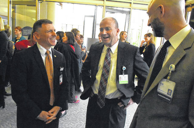 Dr. David Cohn, left, Dr. Chris Rhoades, and Bob Baxter, president, Mercy Health converse after the St. Rita's Medical Center & the James affiliation announcement on Wednesday morning at St. Rita's Cancer Center.