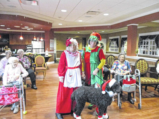 Lynn, the Merry Christmas Dog, with her elf, Sandy Stanfield, and Mrs. Claus, also known as Lynn Ruth, of the Auglaize County Council on Aging, visited residents of Elmwood Assisted Living recently. Lynn, the dog, enjoyed pets and pats by the residents.