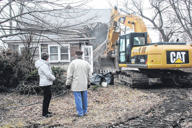 Michael and Lois Jamieson, of Springfield, watch as Dave Nagel Excavating employee Alan Saintignon, of New Bremen, starts tearing down a house located next to PNC bank on Michigan Street Saturday morning. Michael and his brother, David Jamieson, of Canada, grew up in the house.