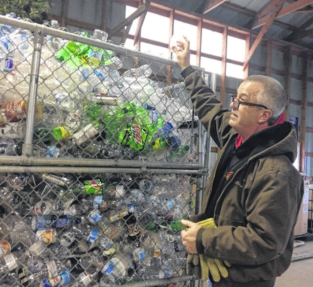 New Bremen Village Councilman Jim Kronenberger looks at a bin filled with plastic bottles at the New Bremen Recycling Center. Kronenberger and other volunteers are learning about the changes coming with new recycling rules.