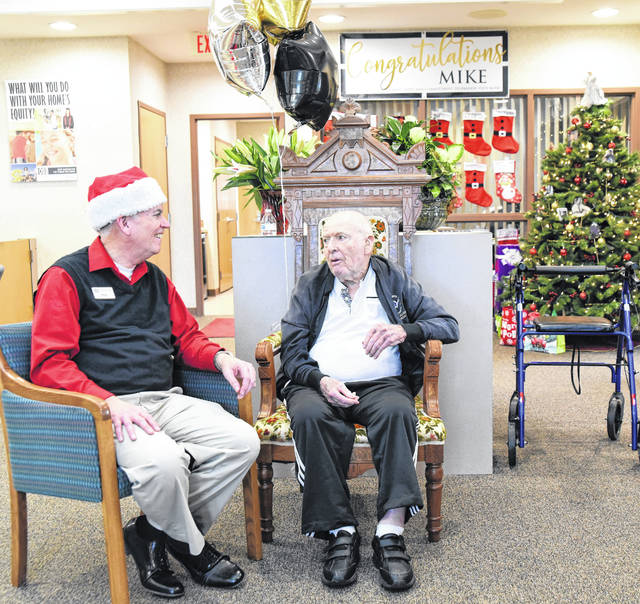 Michael Monnier, left, of Sidney, gets advice on life after work from his father, Norris Monnier, 93, of Sidney, during a reception in the Fort Loramie branch of the Osgood State Bank, celebrating Michael's retirement as President/CEO of OSB Bancorp Inc., the Osgood State Bank holding company, Wednesday, Dec. 19.