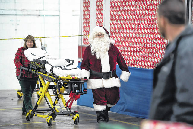 Deb Hathaway, of Greenville, is escorted by Santa, himself, as Spirit Medical Transport Vice President Aaron L. Guthrie (forefront) watches the arrival of the first of six power cots purchase by Spirit as a holiday surprise for the staff. Hathaway works in the billing and quality assurance departments of Spirit and is the mother of co-owner Brian K. Hathaway.