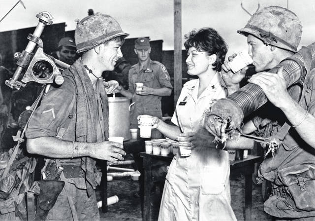 July 31, 1966. Bien Hoa, South Vietnam. SP/4 John V. Russel, left, of Landrum, South Carolina, and PFC Robert Wooldridge, right, of Newton, Iowa, both members of C Company, 1ST Battalion, 503D Infantry of the 173D Airborne Brigade, drink coffee and talk with Beckey Fey of Blackwell, Oklahoma, the American Red Cross Clubmobile director with the 173D. C Company had just returned to Bien Hoa by helicopter after six weeks in the field. Photo by U. S. Army