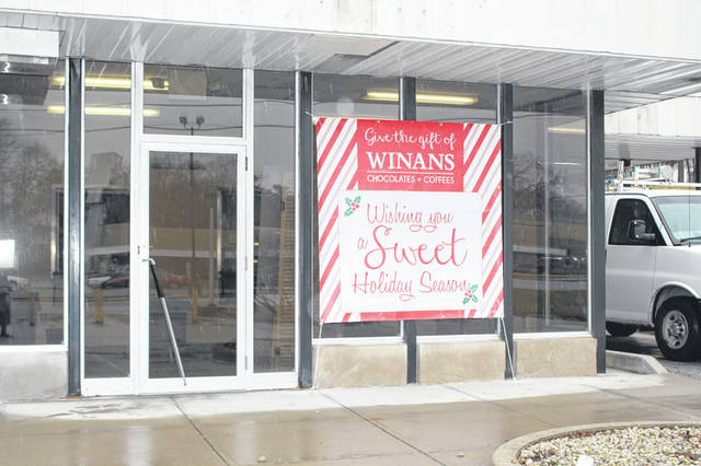 A sign on a former bank building along Wapakoneta Avenue teased passersby, Thursday, Dec. 20. Winans Chocolates & Coffees will open there in the spring.