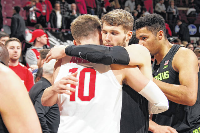Ohio State University basketball player Justin Ahrens and his brother, Kyle Ahrens, who plays for Michigan State University, hug after Saturday's basketball game in Columbus. More than 400 friends and family members of the Versailles brothers traveled to Columbus for the game.