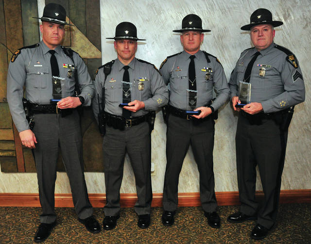 "Mike Ullery | Daily Call Ohio State Highway Patrol Troopers Jason Hutchison, Charles ""Chip"" Gannon, Jim Davis, and Sgt. Dave Robison, left to right, pose with their awards for heroism presented by Piqua City Schools for the troopers' part in saving the lives of two Piqua City Schools employees following a crash on I-75 in December. Hutchison and Gannon are from the Dayton Post of the Ohio State Highway Patrol, while Davis and Robison are assigned to the Piqua Post."