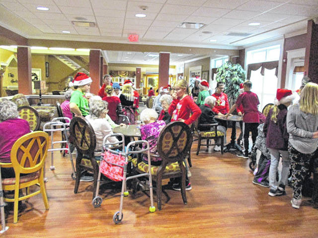 Fifth-grade students from New Bremen Local Schools visit with residents of Elmwood Assisted Living in New Bremen, recently. The children also played games with and read to residents.