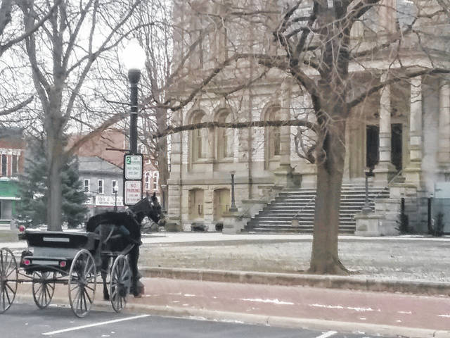 A lone horse and buggy is parked along West Poplar Street in front of the Shelby County Courthouse in Sidney. More than 60 members of area Amish communities and their neighbors filled the courtroom for a settlement hearing, Friday, Jan. 11. Seven families are defendants in civil lawsuits brought by the local health board regarding non-compliant waste systems.