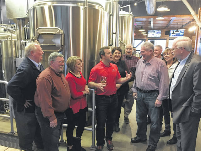 Members of the Shelby County Bicentennial Beer Subcommittee listen as Moeller Brew Barn Brew Master Nick Moeller, fourth from left, talks about the brewing process Friday, Jan. 25.