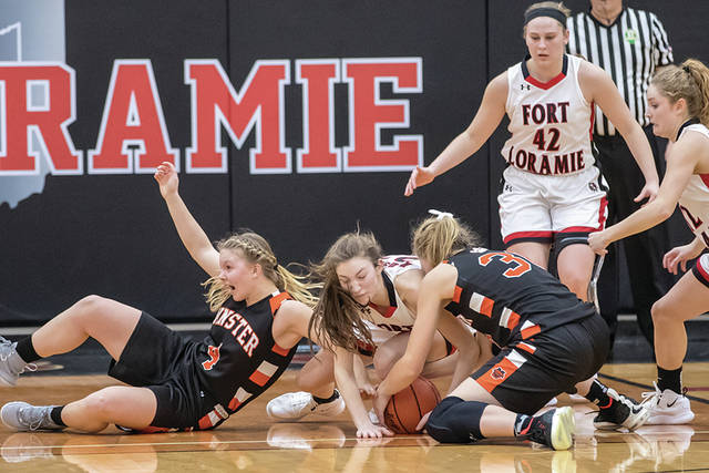 The Fort Loramie and Minster girls basketball teams battle for a loose ball Saturday.