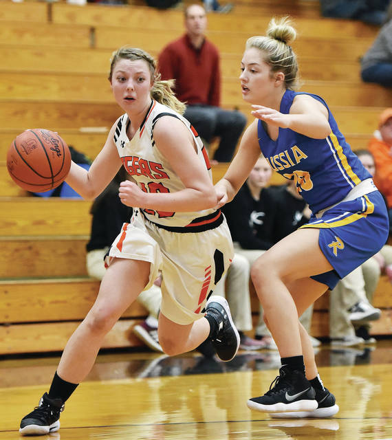 Jackson Center's Kylie Hartle drives past Russia's Ashley Scott during a Shelby County Athletic League game on Thursday in Jackson Center.
