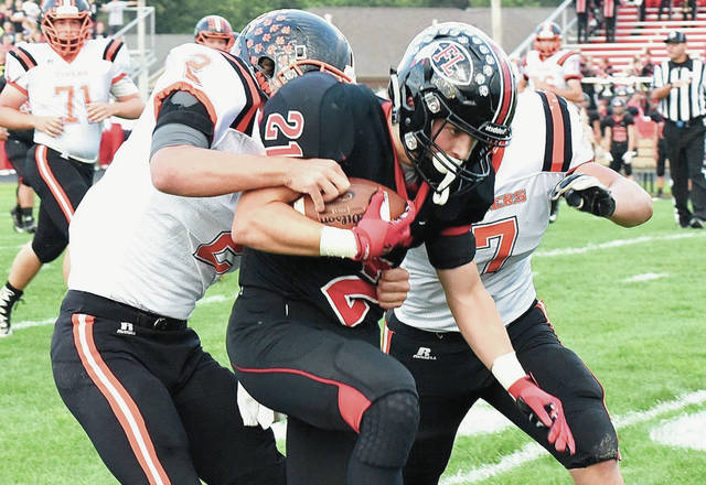 Fort Loramie running back Carter Mescher runs while being taken down by two Ansonia defenders during a Cross County Conference game on Sept. 21, 2018 in Fort Loramie. Ansonia is one of several schools that may vote to leave the CCC early next month.