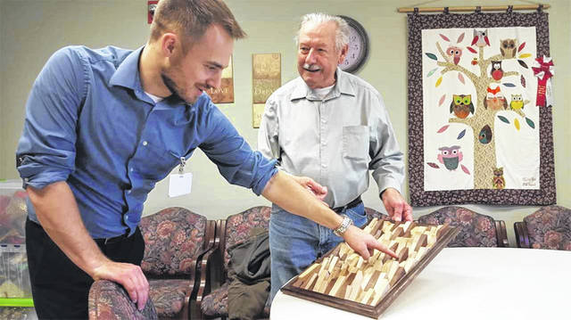 "John Apple, right, of Sidney, explains his folk art piece, ""Wedges,"" to Eric Shoemaker, director of independent living at Ohio Living Dorothy Love, recently. Apple will display ""Wedges"" and other works in the Hobby and Woodworking Show at Dorothy Love, Wednesday, Jan. 23."