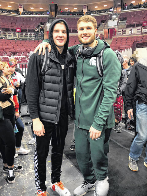 Justin, left, and Kyle Ahrens relax after Saturday's basketball game between Michigan State University and Ohio State University. The elder Ahrens' team defeated the Buckeyes in Big 10 play.