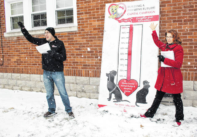 SCARF members Joe Laber, left, and Julie Ehemann celebrate the reaching of the $2.4 million goal for the new animal shelter and adoption center Saturday morning, Jan. 12. The Bob Sargeant and Family Animal Shelter and Adoption Center is being built on Gearhart Road.