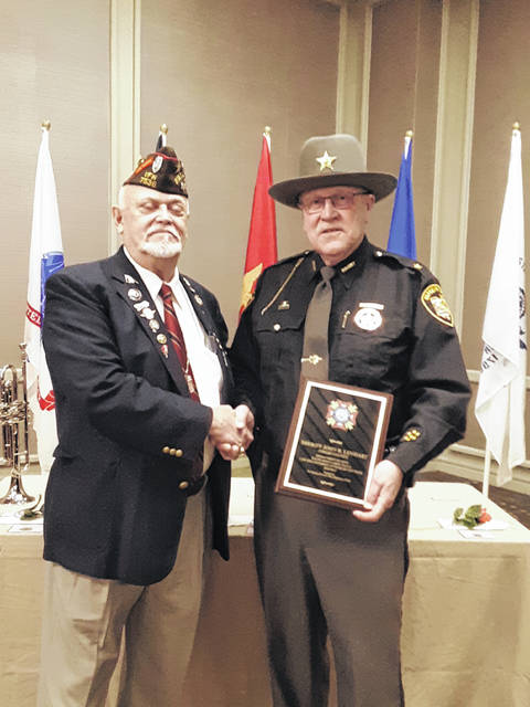Ohio Veterans of War Commissioner Clayton Uzell presents the Ohio Law Enforcement Officer of the Year award to Shelby County Sheriff John Lenhart Saturday, Jan. 12, in Columbus.