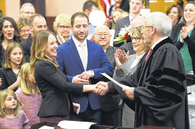 Susan Manchester, R-Waynesfield, was sworn into office Monday as the Ohio House's 84th District representative. Shaking her hand after the ceremony is Ohio Supreme Court Judge Patrick J. Fischer, as Manchester's finance Isaac Gray and her mother, Martha Manchester,look on.