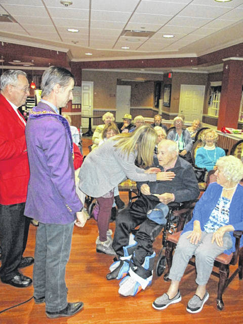 Jonny Dicke, left to right, secretary of St. Marys Council No. 81 Royal Arch Masons, and Mike Terry, grand conductor of the Grand Council of Ohio Royal and Select Masons, watch as Beni Menker, of St. Marys, pins an award on her father, Benjamin Frasure, of New Bremen, at Elmwood Assisted Living in New Bremen, Friday, Jan. 11. At right is Frasure's wife of 75 years, Patsy. Frasure was honored for 60 years of Masonic membership.