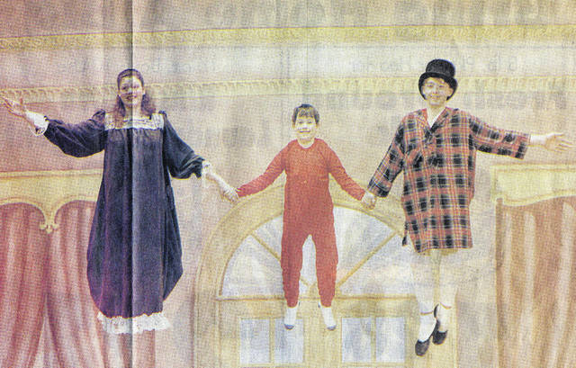 "Jill (Westerheide) Larger, left, flies above the Sidney High School stage as Wendy in a 1994 Sidney Dance Company production of ""Peter Pan."" Also pictured are Michael Eikenberry and Jason Henschen."