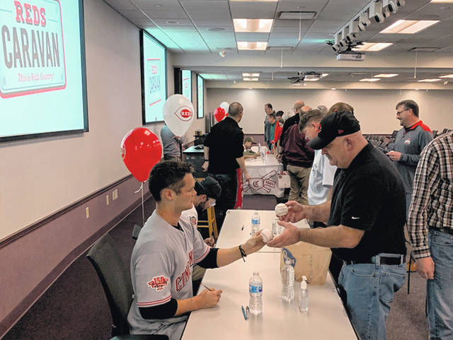 Cincinnati Reds player Brantley Bell, left, signs baseballs for Emerson Climate Technologies employee Jim Duncan, of Sidney. Duncan got five baseballs signed for his family members while Reds players visited Emerson on their North Caravan Tour, Friday, Jan. 18.