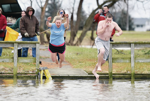 Tylor McGee, left, of Letterkenny, Ireland, and John Grusenmeyer, of Tipp City, jump into Lake Loramie Tuesday, Jan. 1. Others who jumped in were Thomas Langenkamp, of Coldwater, Travis Chmiel, of Dayton, Rev. Jacob Willig, of Cincinnati, and Rev. Ethan Moore, of Huber Heights. Moore organized the annual jump to dedicate the new year to Jesus through his mother Mary on her feast day. The lake was high due to heavy rains the day before.