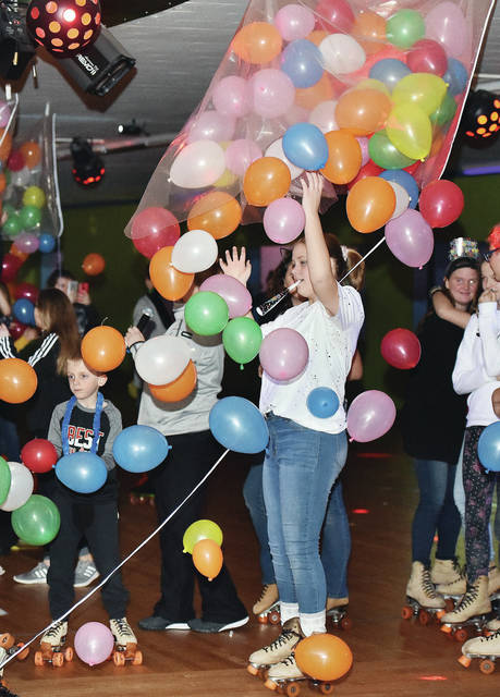 Balloons drop on Brayden Leach, left, 10, of Sidney, son of Aaron Leach and Melanie Hennon, and Issabelle VanMeter, 11, of Anna, daughter of Chris VanMeter and Myndi VanMeter, at Rolling Hills Skate as the clock strikes 12 a.m. Tuesday, Jan. 1. Roughly 130 kids played games, held races, and were handed raffle prizes during a New Year's bash at Rolling Hills Skate.