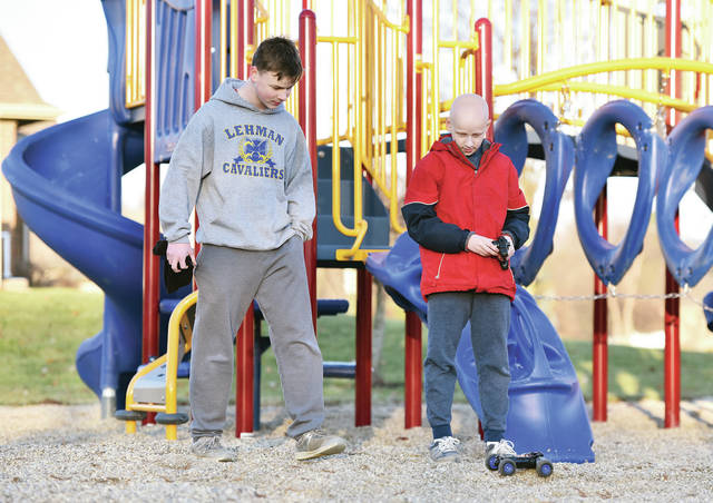Noel Petersen, left, 13, watches as his brother, Henry Petersen, 11, sons of Julie and Joe Petersen, of Sidney, takes a remote-controlled car for a spin in Plum Ridge Park in Sidney. The brothers took advantage of a sunny day Thursday, Jan. 3, to bike to the park and play with the car.