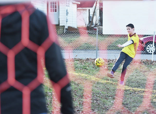 Zen Wagner, right, 12, tries to score as his dad, Jerry Wagner, defends a goal in their backyard in Jackson Center Saturday, Jan. 6. The warm weather brought them outside so Zen could practice his soccer skills. Zen plays for the Jackson Center Youth Sports Organization and Lima Extreme. Zen is also the son of Linda Wagner.
