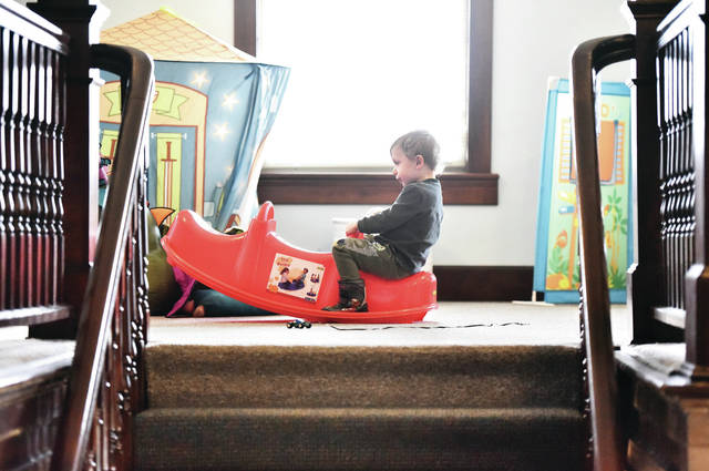 Liam Flood, 3, of Sidney, son of Scott and Cheryl Flood, attempts to rock on a Trio Rocker by himself at the Minster Stallo Library Tuesday, Jan. 8. Liam was waiting for Catholic Schoolhouse Home School Coop to start at 1 p.m. The classes are held at the library.