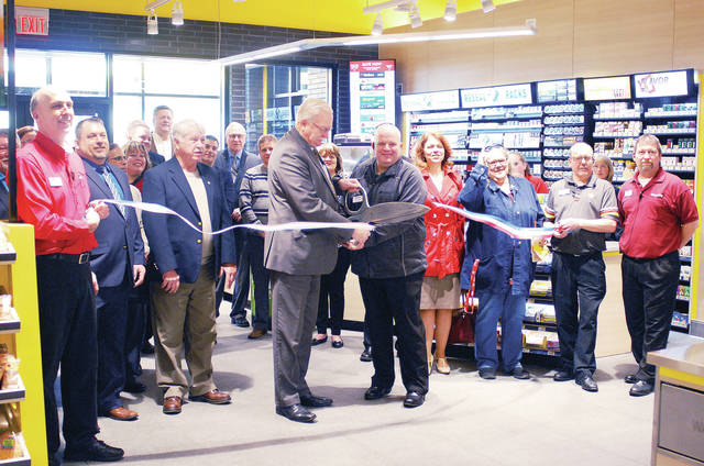 Sidney Mayor Mike Barhorst, center left, and Love's General Manager Todd Turner, second from left, of Sidney, cut a ribbon during a grand opening ceremony and ribbon cutting held Tuesday, Jan. 8.