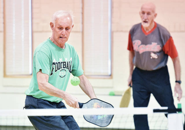 Dave Bell, left, prepares to swing as his pickleball partner, Ron Argabright, watches at the Senior Center of Sidney-Shelby County, Friday, Jan. 18. Both men are from Sidney.