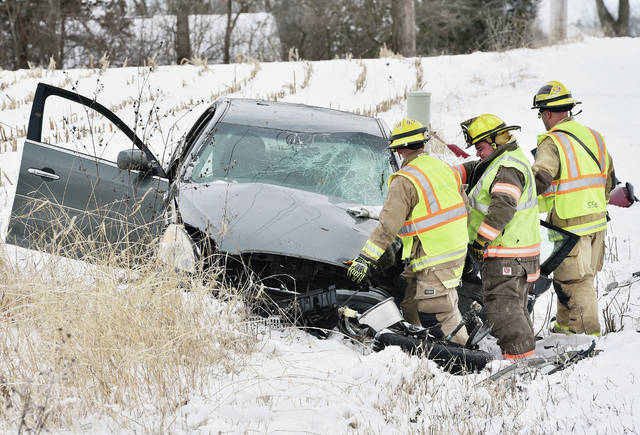 Firefighters look at the grey 2007 Buick Century, of which they had just extricated a man from, with help of the jaws of life. The vehicle collided with a red 2012 GMC Arcadia SUV on the 16000 block of East Mason Road, north of Sidney, at 10:42 a.m. Tuesday, Jan. 22. Sidney and Port Jefferson firefighters responded. The Shelby County Sheriff's Office is investigating the crash.